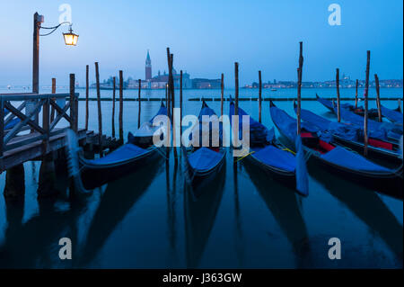 Dawn view of gondolas moored in Venice , Italy - Stock Photo