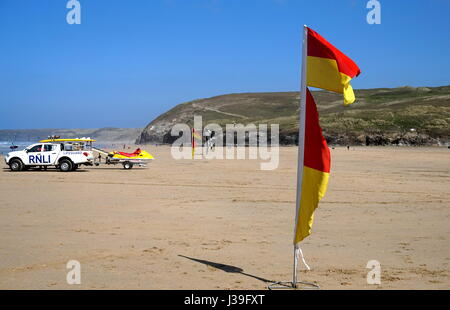 Newquay, Cornwall, UK - April 7 2017: Warning flags on the beach for swimmers and surfers, with RNLI Lifeguard truck - Stock Photo