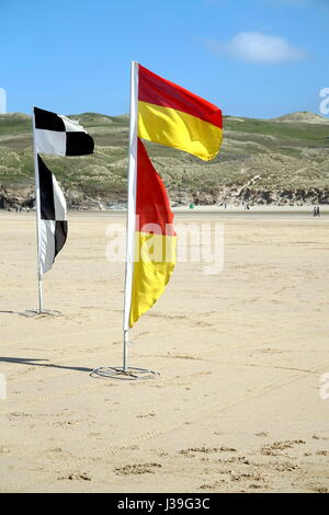Newquay, Cornwall, UK - April 7 2017: Warning flags on the beach for swimmers and surfers - Stock Photo