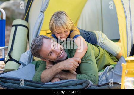 Playful little boy lying on father in tent at campsite - Stock Photo