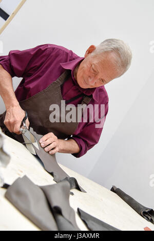 Paris. 3rd May, 2017. An artisan demonstrates the production process of leather goods during the 3rd International - Stock Photo