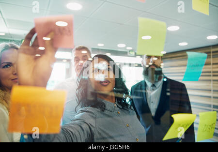 Businesswoman putting sticky note on glass, group of colleagues behind her - Stock Photo