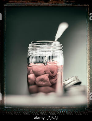 peppers in a glass jar with a spoon - Stock Photo
