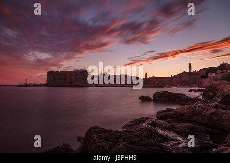 The early summer sunshine dips below the horizon as the sky turns pink over Dubrovnik and its old harbour. - Stock Photo