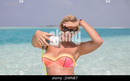 Pretty woman is making selfie on the beach - Stock Photo