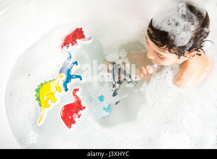 Boy playing with toys in bath, elevated view - Stock Photo