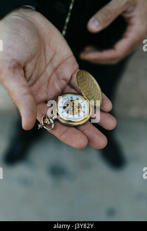 Man wearing suit, holding pocket watch in hand, elevated view, close-up - Stock Photo