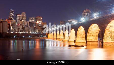 The Stone Arch Bridge dominates the night scene in Saint Paul Minnesota - Stock Photo