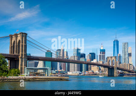 Bright scenic daytime view of the Brooklyn Bridge with the Lower Manhattan skyline across the East River under clear - Stock Photo