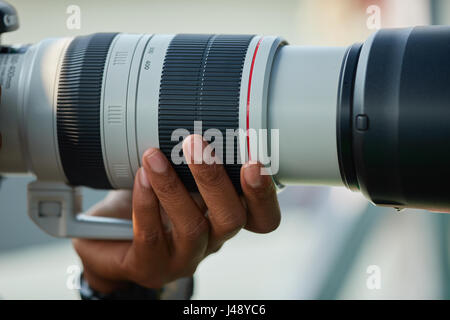 photographer with camera in hand looking through the camera lens - Stock Photo