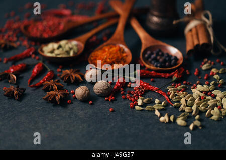 Aromatic spices in wood spoons on dark stone background - Stock Photo