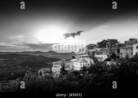 Black & White image of ancient hilltop village of Belgodere in the Balagne region of Corsica lit up by a dramatic - Stock Photo