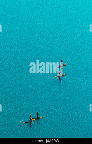Aerial view of unrecognizable group of people stand up paddle boarding on water surface for sport, fun, leisure - Stock Photo