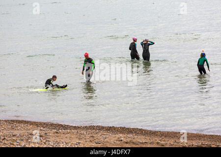 Group of people wearing wetsuits enjoying themselves in the sea at Weymouth, Dorset in May - Stock Photo