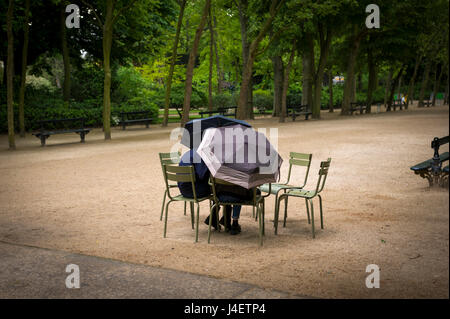 Young couple hiding under umbrellas in Luxembourg Gardens - Stock Photo