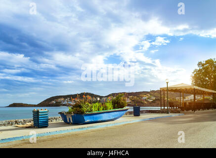 Old fishing boat stands on the shore and decorated by a flower bed. Tourist attraction Livadi beach in sea bay of - Stock Photo