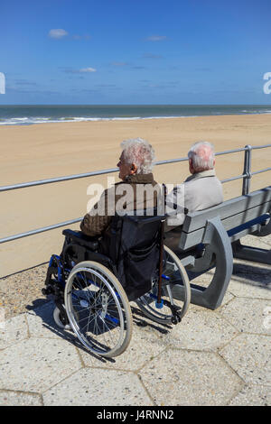 Disabled elderly woman in wheelchair and retired husband sitting on a bench at promenade along the coast on a cold - Stock Photo