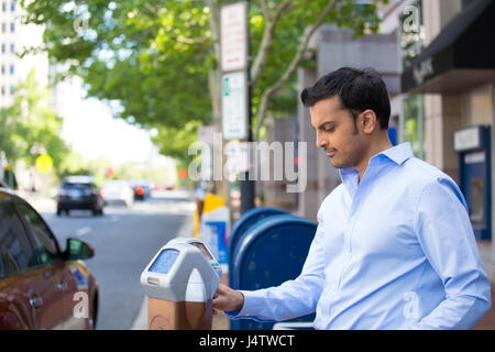 Closeup portrait, young man in blue button down shirt putting coins in parking meter outside to prevent fines, isolated - Stock Photo