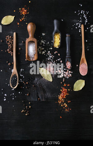 Variety of different colorful salt yellow saffron, pink, black himalayan, white sea and fleur de sel in wooden spoons - Stock Photo