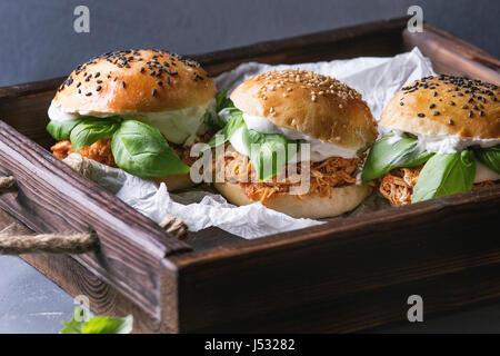 Homemade mini burgers with pulled chicken, basil, mozzarella cheese and yogurt sauce on wooden tray with baking - Stock Photo