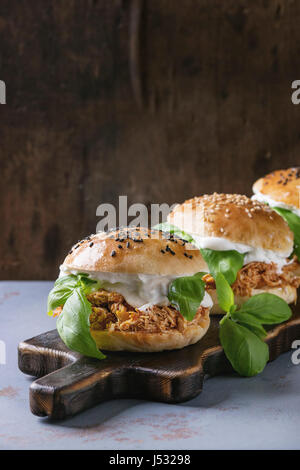 Homemade mini burgers with pulled chicken, basil, mozzarella cheese and yogurt sauce on wooden serving board over - Stock Photo