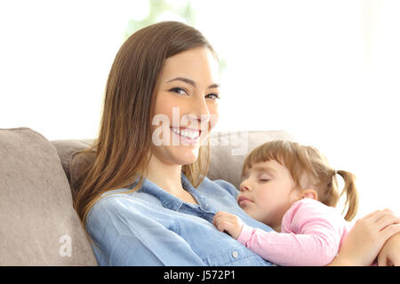 Mother looking at you with her daughter sleeping over her chest sitting on a couch at home - Stock Photo