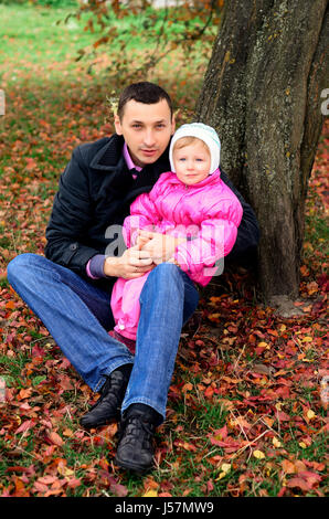 Father and daughter sitting under a tree Fall. - Stock Photo