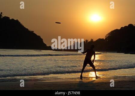 Man playing Frisbee on Palolem beach, South India, Goa, Agonda, Arambol, Anjuna,Cola sea side at sunset - Stock Photo