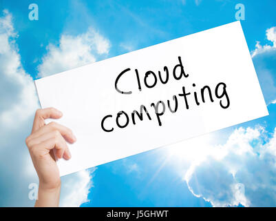 Cloud computing Sign on white paper. Man Hand Holding Paper with text. Isolated on sky background.  Business concept. - Stock Photo