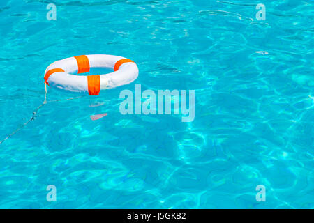 Life buoy in swimming pool - Stock Photo