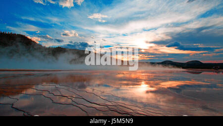 Grand Prismatic Spring at sunset in the Midway Geyser Basin in Yellowstone National Park in Wyoming USA - Stock Photo