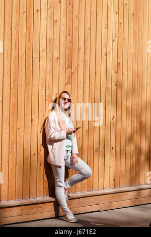 Long-haired blonde full-length with phone - Stock Photo
