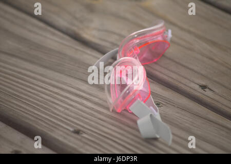 Pair of child's pink swim goggles laying on a wooden deck. - Stock Photo