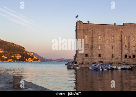 St Johns Fortress drenched in golden light on the edge of the old harbour in Dubrovnik at dusk.  The complex monumental - Stock Photo