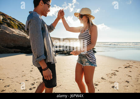 Shot of young man and woman dancing on the beach on a summer day. Romantic young couple dancing on the beach. - Stock Photo