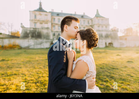 The groom is kissing the beautiful bride in the forehead at the background of the antique gothic castle. during - Stock Photo