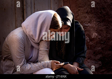 Girls playing with smartphone, Abyaneh, Iran - Stock Photo