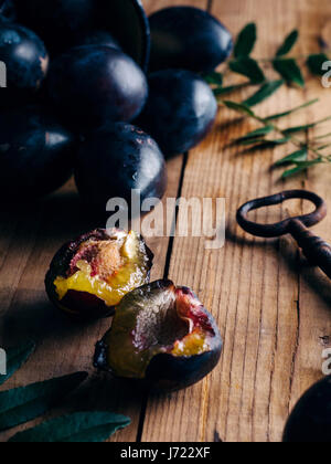 Fresh plums on rustic wooden table - Stock Photo