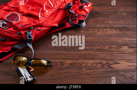 Tourist backpack, sunglasses and gear for the bicycle on the wooden background. - Stock Photo