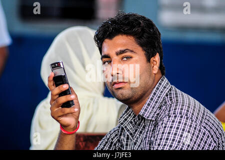 Pathankot, India, september 9, 2010: Portrait of indian man with cellphone. - Stock Photo