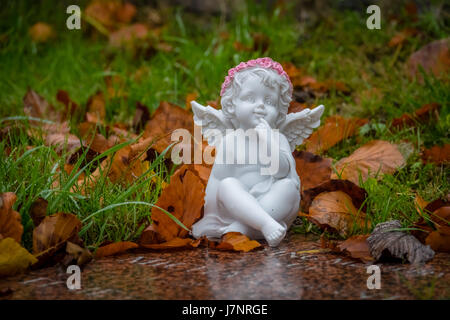Tiny angel figure next to a child grave in cemetery - Stock Photo