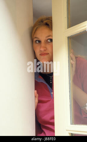 young woman looking suspiciously out of window - Stock Photo