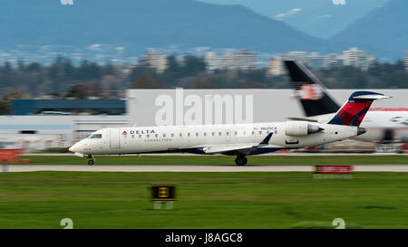Delta Connection (SkyWest Airlines) Bombardier CRJ-700 regional jet takes off from Vancouver International Airport - Stock Photo