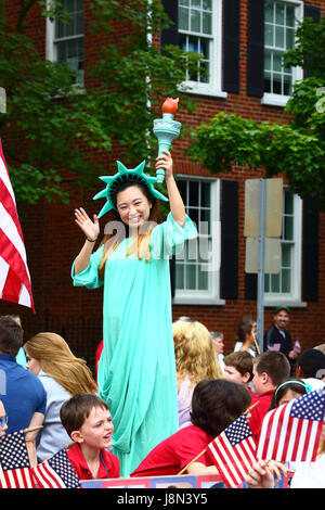 Westminster, Maryland, USA. 29th May, 2017. An Asian American girl dressed as the Statue of Liberty waves to spectators - Stock Photo