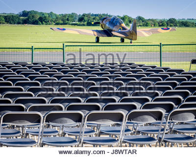 Seating setup ready for visitors to an airshow at Duxford Imperial War Museum in Cambridgeshire, UK. A Harvard aircraft - Stock Photo
