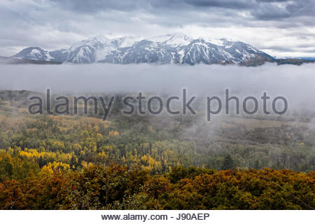 Fog hangs over a mountain valley in the Colorado Rocky Mountains - Stock Photo