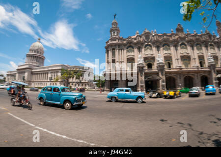 Bright wide-angle view of the daily life on one of the main streets in central Havana, Cuba with classic taxi cars - Stock Photo