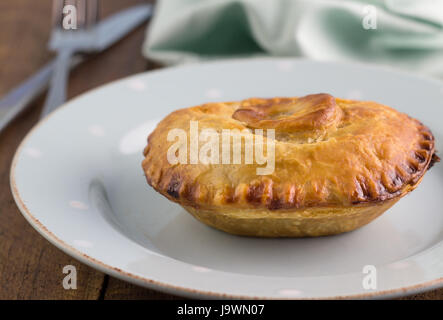 Steak meat pie with gravy - Beef pie in puff pastry close up on plate - Food background - Stock Photo