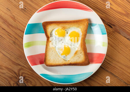 fried quail eggs in a toast on wooden background - Stock Photo