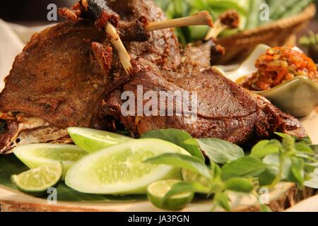 Bebek Goreng, a Popular Indonesian Dish of Fried Duck, Served with Red Chili Paste - Stock Photo